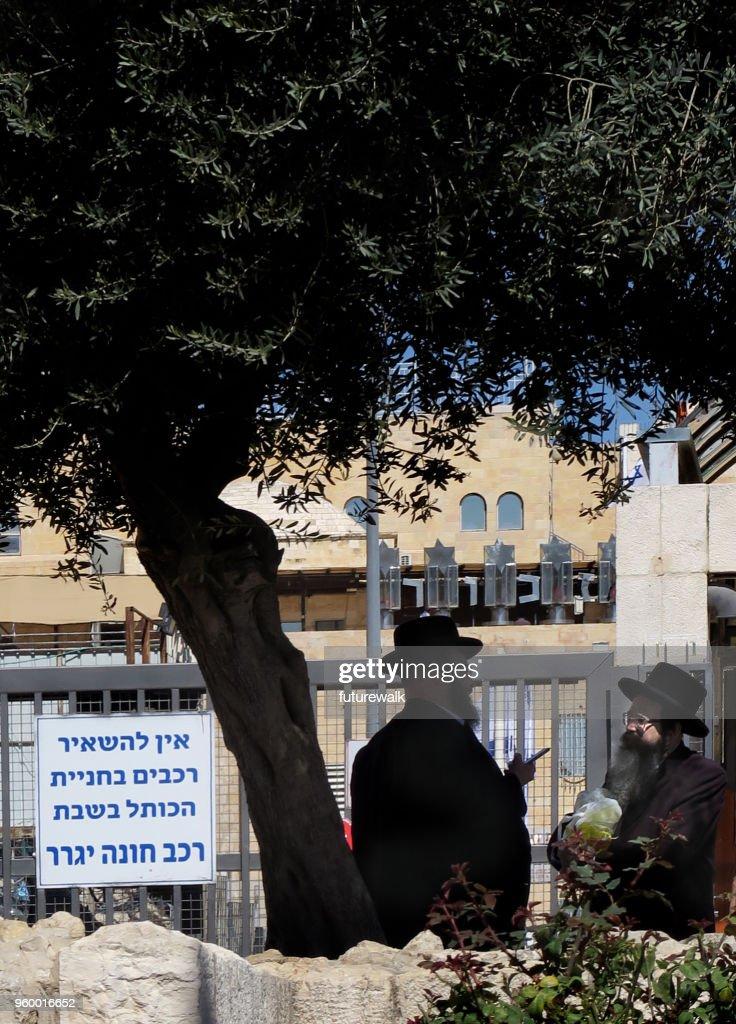 zwei ultra orthodoxe jüdische Männer in traditioneller Kleidung mit einem Gespräch auf dem Bürgersteig in der orthodoxen Viertel in der Innenstadt von Jerusalem, Israel, 7. März 2018 : Stock-Foto