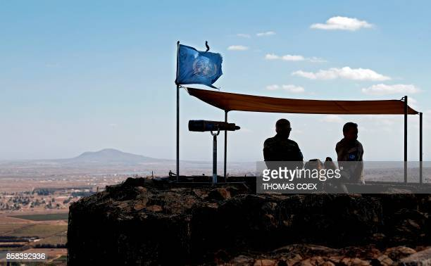 Two UN peacekeepers observe the IsraeliSyrian border from an outpost on Mount Bental in the Israeliannexed Golan Heights on October 6 2017
