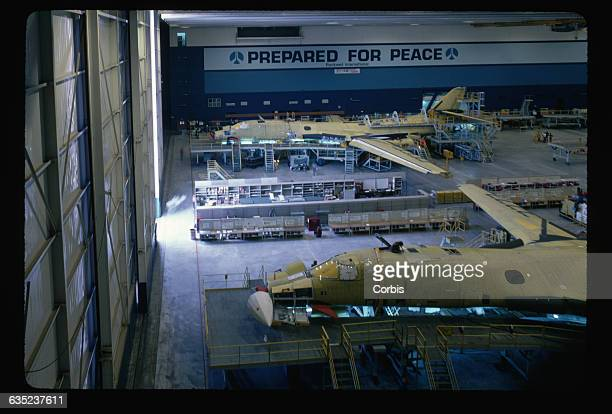 Two unfinished B1B Lancer bombers in an assembly plant at Air Force Plant 42 California A sign on the wall reads Prepared for Peace