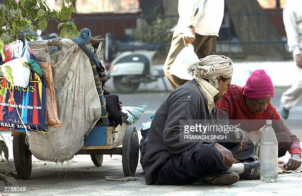 Two unidentied homeless Indian men chat as they sit on a pavement with their belongings in New Delhi 06 December 2003 With temperatures plummeting...