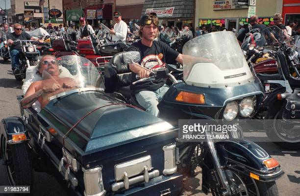 Two unidentified bikers roll down main street on a cycle outfitted with a sidecar made from a coffin during the 61st annual motorcycle rally held...