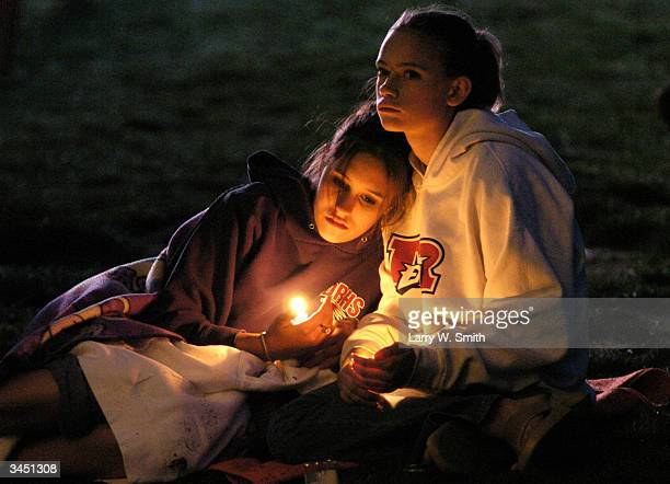 Two unidentified girls attend a candlelight vigil April 20 2004 in Littleton Colorado on the five year anniversary of the Columbine High School...