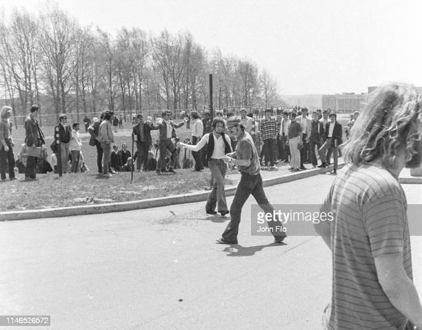 Two unidentified Kent State University students, one with a black flag, as they walk near Jeffrey Miller's blood on the pavement after the Ohio...