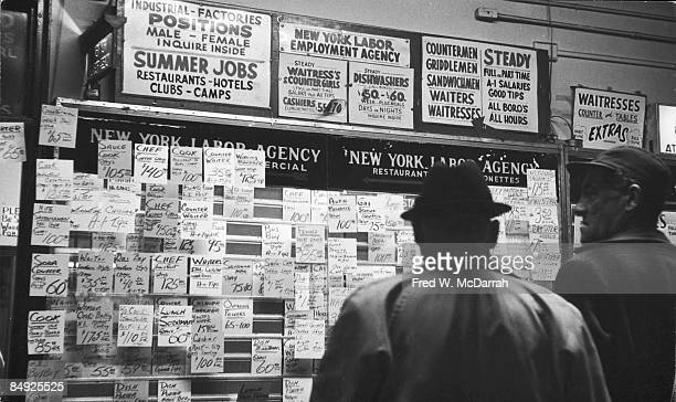 Two unidentified men read the offerings from the job board at a New York Labor Agency office in lower Manhattan New York New York January 22 1964