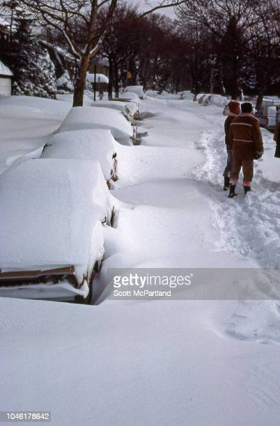 Two unidentified people stand in the middle of a snowcovered residential street in the aftermath of a blizzard Queens New York New York February 13...