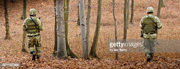 Two Unidentified Soldiers In Camouflage Walks Through Forest