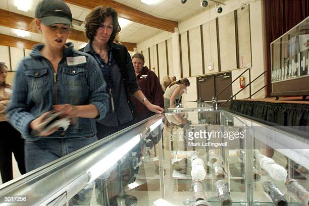 Two unidentified women look into a glass display case at the Jefferson County Fairgrounds which holds several pipe bombs and other weapons collected...