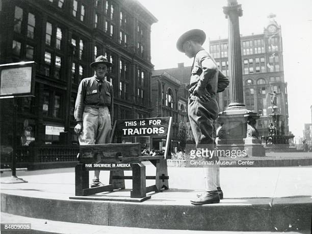 Two uniformed military men stand next to wooden stocks located in Cincinnati's Fountain Square 1917 Signs on the stocks read 'This is for Traitors'...