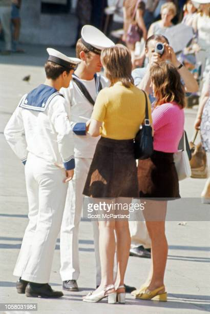 Two uniformed sailors talk with a pair of women both dressed in bright tops and miniskirts Siena Italy August 1968