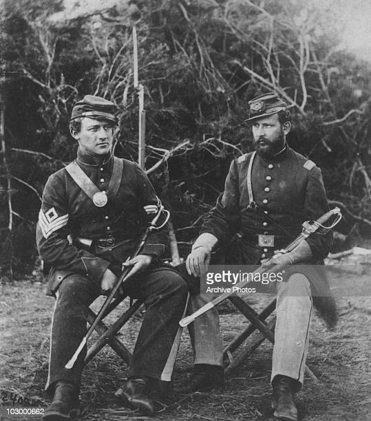 Two Union soldiers of the 31st Pennsylvania Regiment seated with swords during the US civil war circa 1861