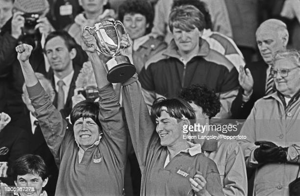 Two United States players celebrate with the trophy after the United States team beat England 19-9 in the final of the 1991 Women's Rugby World Cup...