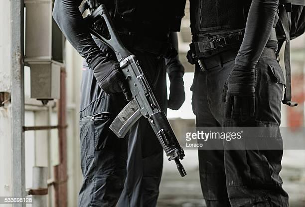 Two unknown swat team members posing in urban setting