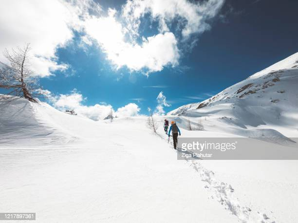 two unrecognizable people on a winter hike - slovenia stock pictures, royalty-free photos & images