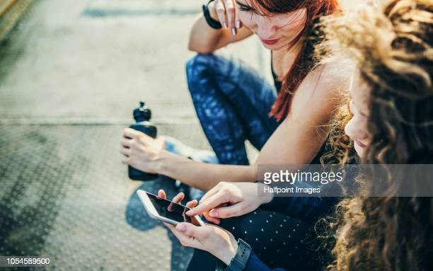 Two unrecognizable sporty friends sitting on a bridge outdoors in the city, using smartphone.