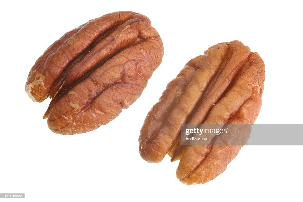 Two unshelled pecans on white background : Stock Photo
