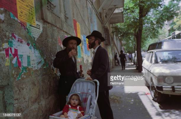 Two unspecified Jewish men, both dressed in black suits with black hats, stand with a pushchair, beside a wall with torn fragments of posters still...