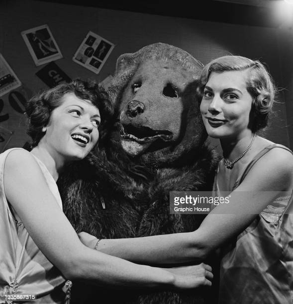 Two unspecified women embrace a person wearing a bear costume at a party, location unspecified, 1955.