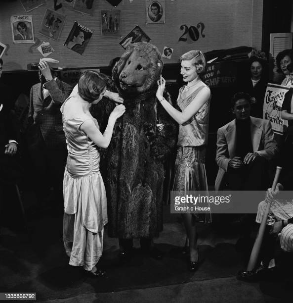 Two unspecified women standing on either side of a person wearing a bear costume at a party, location unspecified, 1955. Covers of 'Theatre Magazine'...