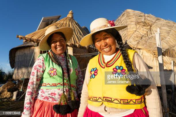 two uros women with braids and wearing colourful local traditional clothing on their floating island near puno, lake titicaca, peru (model releases) - cultura peruana fotografías e imágenes de stock