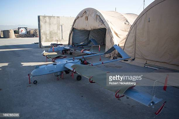Two US Army 14' Shadow surveillance drones sit near a hangar at Forward Operating Base Shank May 8 2013 in Logar Province Afghanistan The Shadow...