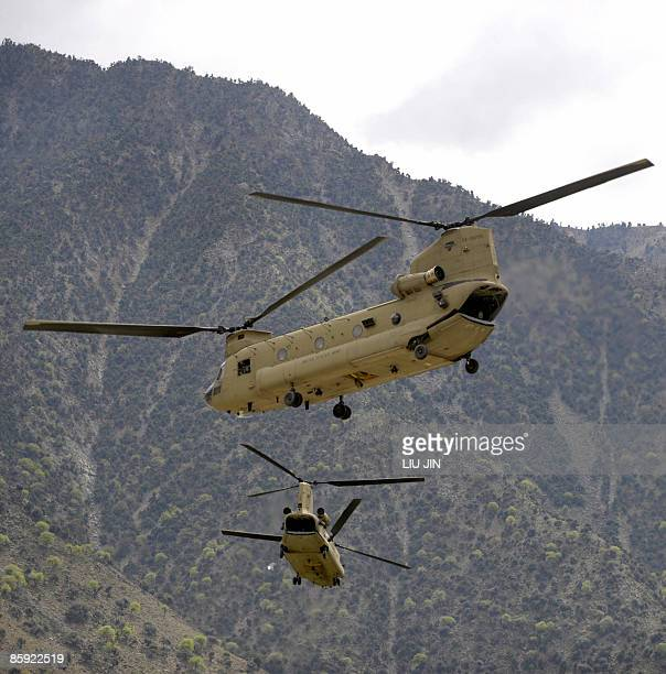 Two US Army CH-47 Chinook helicopters fly over the mountains near the ISAF's Camp Bostick in Naray, in the eastern Kunar province on April 13, 2009....