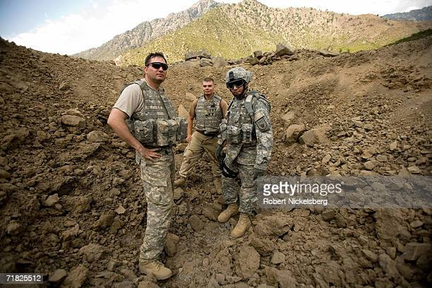 Two US Army soldiers from an Explosives Ordnance Disposal Team along with a US Navy Lieutenant right pose for a picture while checking the results of...