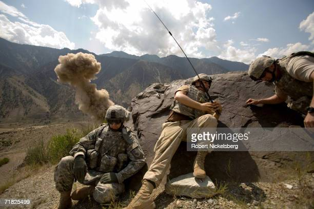 Two US Army soldiers from an Explosives Ordnance Disposal Team , center and right, along with a US Navy Lieutenant, left, take cover as a weapons...