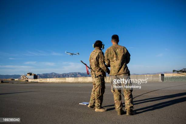 Two US Army soldiers watch as a US Army 14' Shadow surveillance drone is launched at Forward Operating Base Shank May 8, 2013 in Logar Province,...