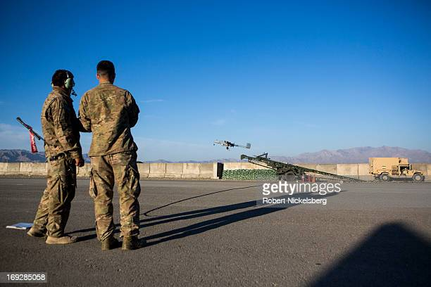 Two US Army soldiers watch as a US Army 14' Shadow surveillance drone is launched at Forward Operating Base Shank May 8 2013 in Logar Province...