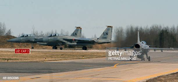 Two US F15C Eagle and JAS39 Gripen aircraft of the Swedish jet fighter prepare for take off during the Lithuanian NATO air force exercise at the air...
