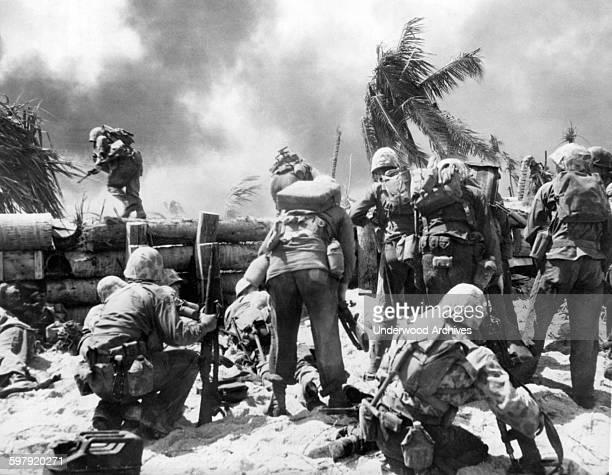Two US Marines go over the Japanese wall fortification during the battle for the Japanese held island of Tarawa Tarawa Gilbert Islands Kiribati...