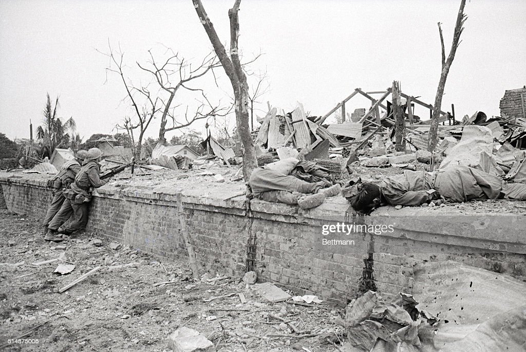 Two US Marines Surveying Destroyed Home : News Photo
