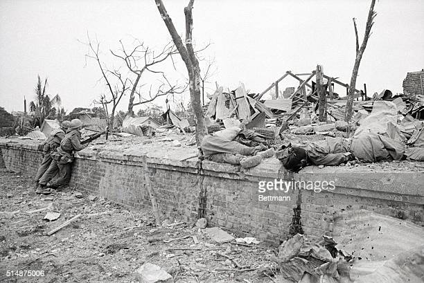 Two US marines lean against the wall of a destroyed home in Hue Vietnam near the bodies of two Vietcong soldiers who were inside at the time of the...