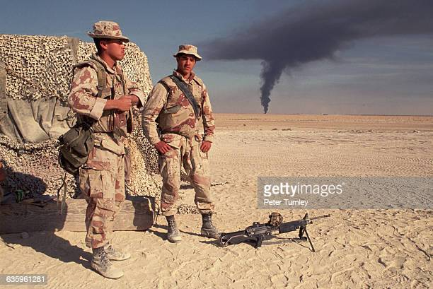 Two US Marines of the Third Battalion watch black smoke from an oil fire ascend from the horizon. As Iraq's forces retreated from Kuwait, Saddam...