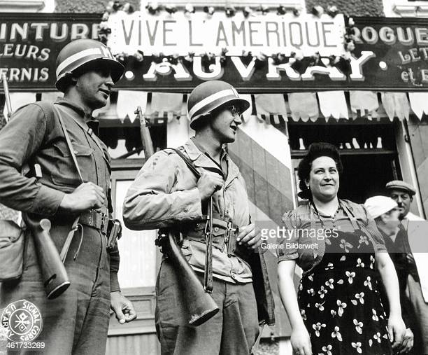 """Two U.S. Military Police stand with a woman under the name of the paint-Drugstore A. Auvray that displays a sign """"Vive L'Amerique"""" . June 1944. Rue..."""