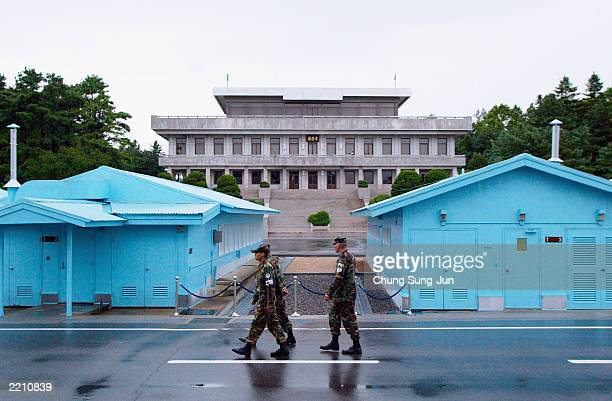 Two US Military Policemen walk with a South Korean soldier July 27 2003 in the border village of Panmunjom in the demilitarized zone between South...