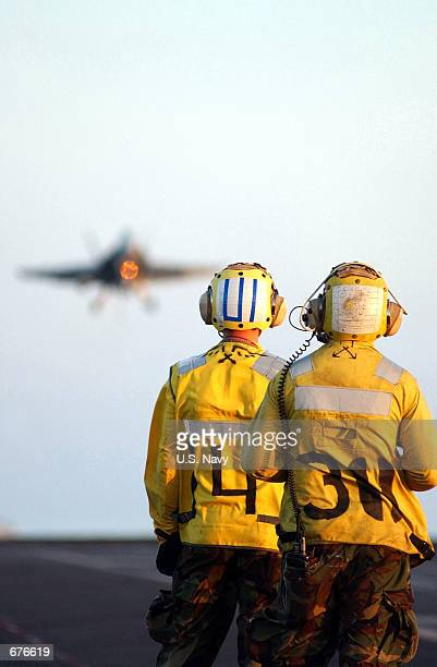 """Two U.S. Naval Aviation Boatswain's Mates await the landing of an F/A-18 """"Hornet"""" aboard the USS Kitty Hawk December 5, 2001 while at sea. The USS..."""