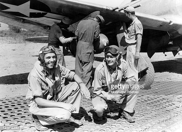 Two US pilots waiting for the loading of the bombs under a P47 Thunderbolt fighter plane before taking part in operation 'Uppercut' Corsica August...
