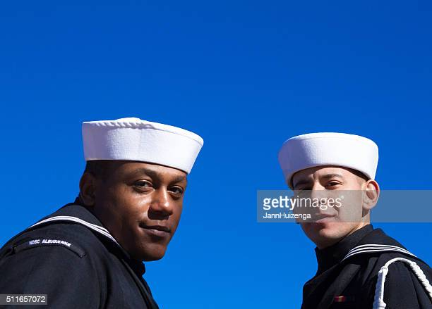 two us sailors at veterans' day memorial service, blue background - veterans day background stock photos and pictures