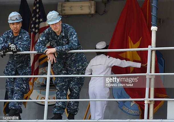 Two US sailors look down as a sailor unfolds a Vietnamese flag aboard the US Seventh Fleet's flagship USS Blue Ridge at Tien Sa port as Vietnam...