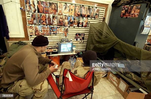 Two US soldiers from the 4th Infantry Division play video games at their base in the Birthday Palace one of the palaces of former Iraqi dictator...