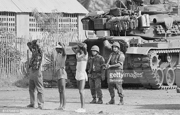 Two US soldiers hold three suspected members of the People's Revolutionary Army at gunpoint in St George's Grenada during the Grenada Invasion