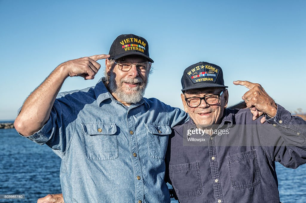 Two USA Military War Veterans Pointing At Souvenir Hats : Stock Photo