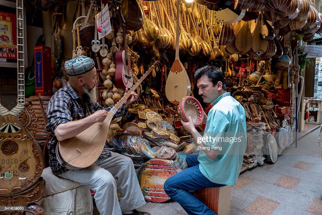 Two Uygur men plays traditional Dutar and hand drum beside a... : Fotografía de noticias