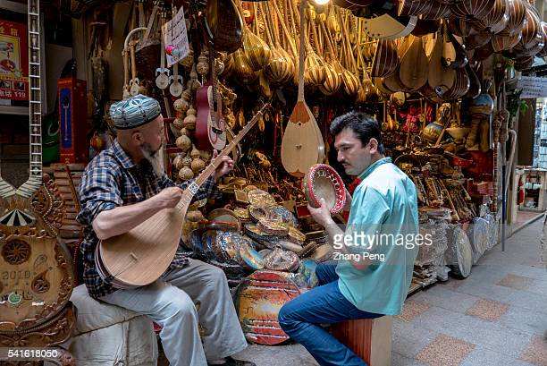 Two Uygur men plays traditional Dutar and hand drum beside a music instruments stall in the Grand Bazaar The Xinjiang International Grand Bazaar an...