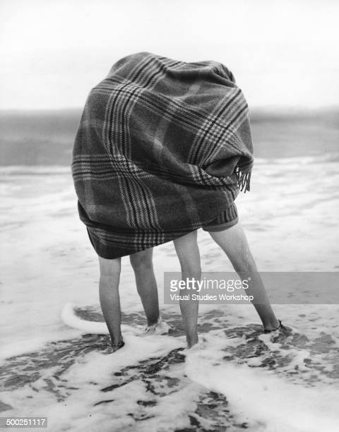 Two vacationers find comfort under a blanket when testing the water to see if it is too cold for a dip early to mid 20th century