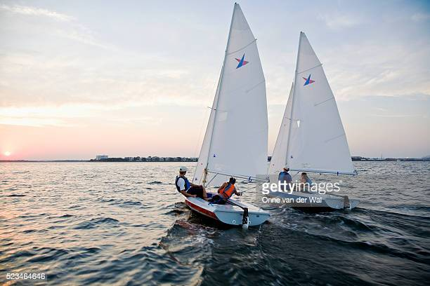 two vanguard 15 sailboats in a friendly sunset race - セーリング ストックフォトと画像