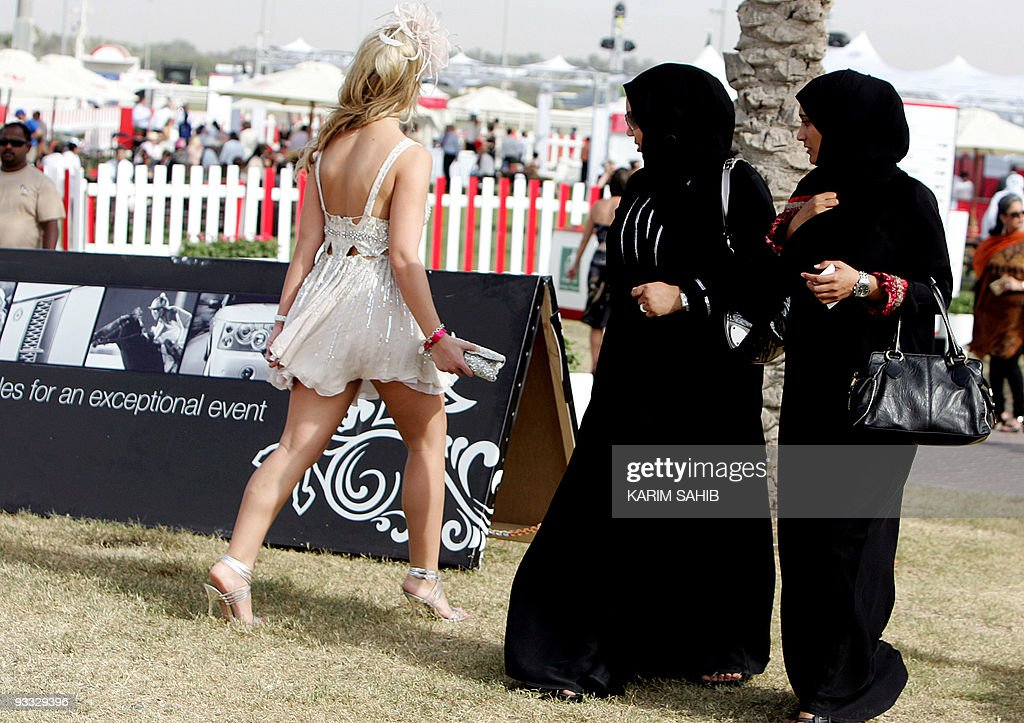 Two veiled Emirati women stare at a foreigner wearing a revealing dress at horse racing's 2008 Dubai World Cup at Nad al-Sheba in Dubai on March 29, 2008. The Dubai World Cup is the richest horse race in the world, with prize money totalling 21.25 million US dollars.