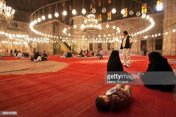 CAIRO EGYPT FEBRUARY 8 Two veiled woman and a baby seat inside the Mosque of Mohammed Ali or Alabaster Mosque in the Citadel on February 8 2006 in...