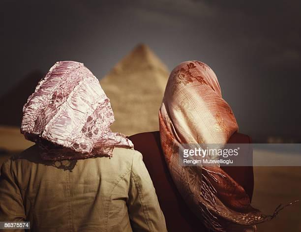 two veiled women and the giza pyramids - kairo stock-fotos und bilder